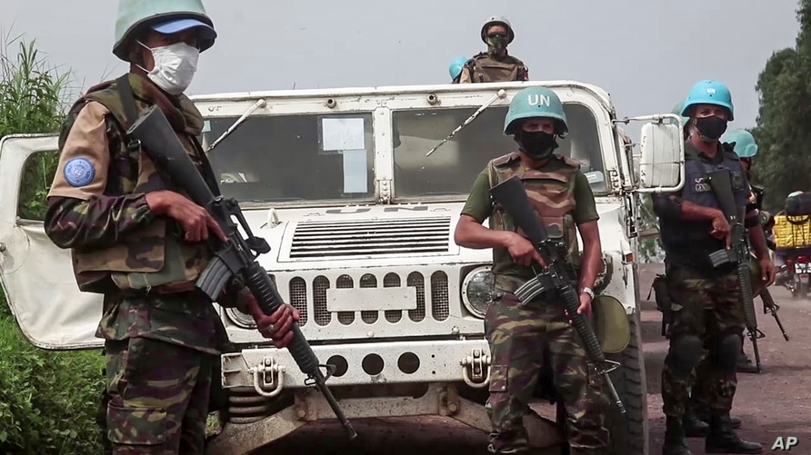 In this image taken from video, United Nations peacekeepers guard the area where a U.N. convoy was attacked