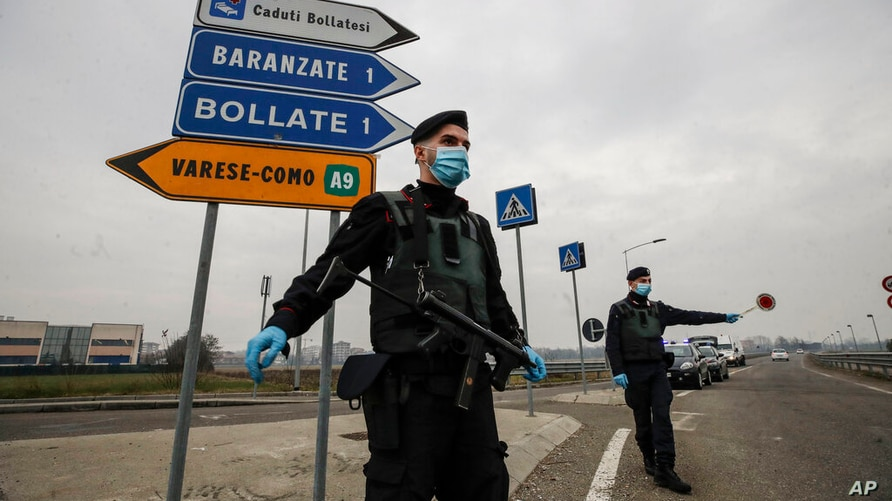FILE - Carabinieri officers patrol one of the main access road to Bollate, in the outskirts of Milan, Italy. Italy's northern…