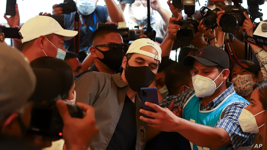 President Nayib Bukele poses for a selfie with a poll worker, as he votes in local and legislative elections at a polling station in San Salvador, El Salvador, Feb. 28, 2021.