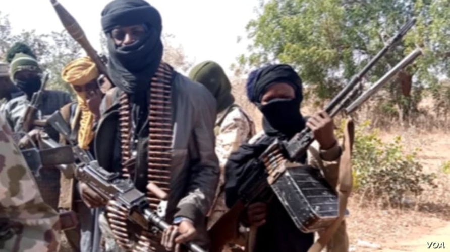 Several people, their faces hidden by scarves, show off rifles and rounds of ammunition.