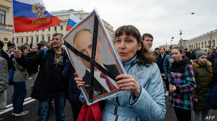 FILE - Opposition activists participate in a rally against Russian President Vladimir Putin, in Saint Petersburg, Russia, May 5, 2018.