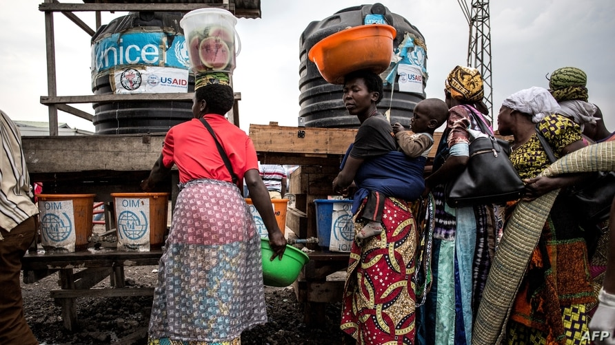FILE - Congolese women are seen lining up to wash their hands and get their temperatures taken at a Ebola screening station on the road between Butembo and Goma, DRC, July 16, 2019.