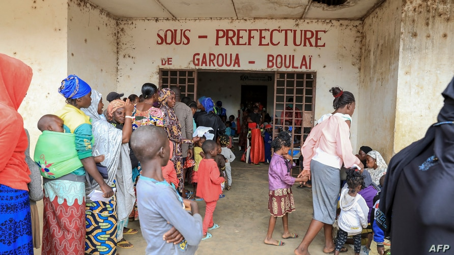 FILE - Refugees from the Central African Republic wait in line to be registered, in front of municipal administrative offices in Garoua-Boulai, Cameroon, Jan. 8, 2021.