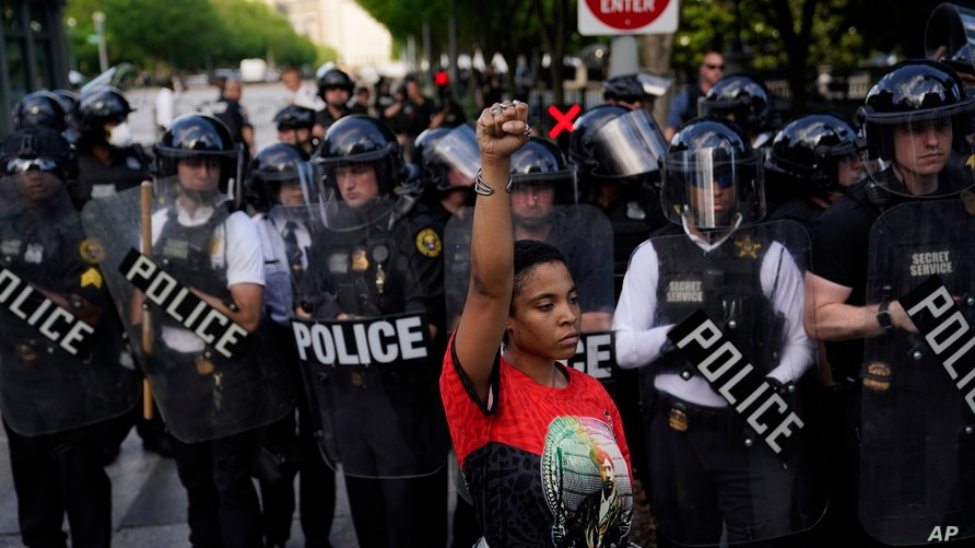 FILE - A demonstrator raises her fist to protest the death of George Floyd, near the White House, in Washington, May 30, 2020. Floyd, an African American, died after being restrained by Minneapolis police officers, triggering nationwide protests.