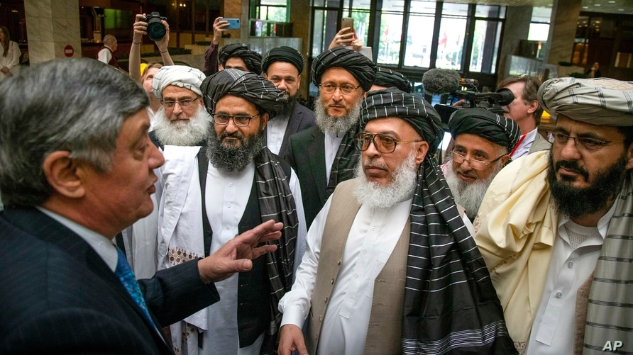 FILE - Russian envoy to Afghanistan Zamir Kabulov, left, speaks with Taliban representatives prior to their talks in Moscow, May 28, 2019.