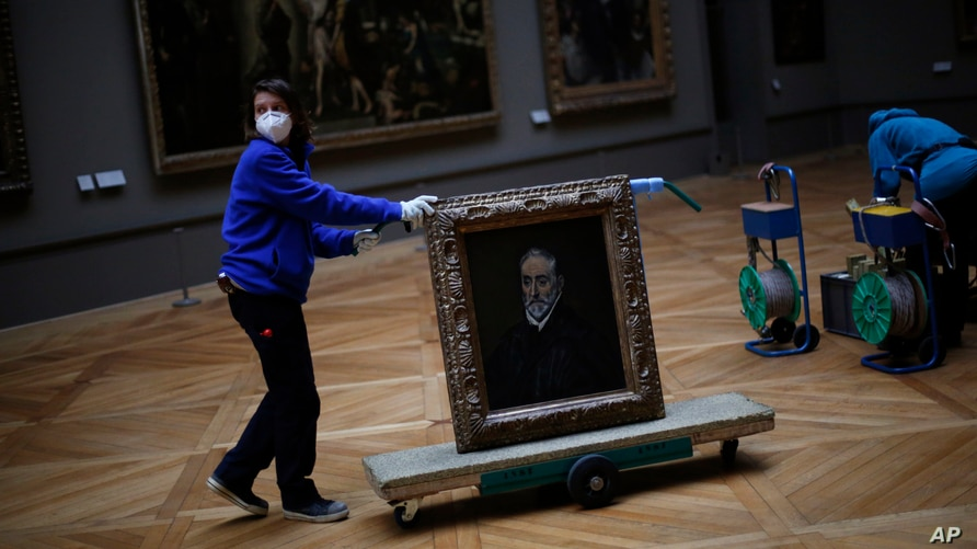 "A worker moves the painting ""Portrait of Antonio de Covarrubias y Leiva"" by Spanish painter El Greco, at the Louvre museum, in Paris, France, Feb. 9, 2021, as the COVID pandemic gives staff a rare opportunity to tackle long-overdue refurbishments."