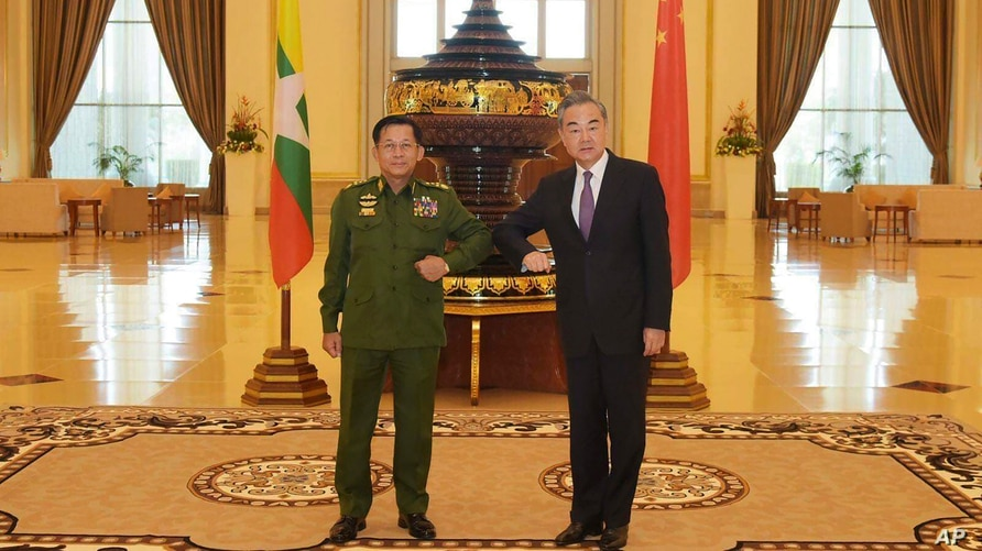 FILE - Myanmar's Army Commander and now the country's new leader, Gen. Min Aung Hlaing, left, and Chinese Foreign Minister Wang Yi pose for a photo during their meeting in Naypyitaw, Myanmar, Jan. 12, 2021. (Myanmar Military Information Team via AP)