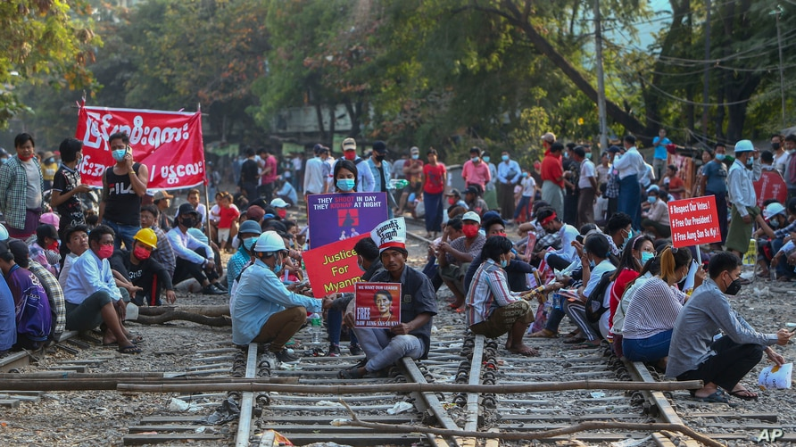 Demonstrators, some holding placards, sit on railway tracks in an attempt to disrupt train service, during a protest against the military coup, in Mandalay, Myanmar, Feb. 17, 2021.