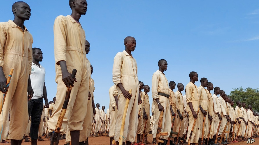 FILE - Men stand at attention with the wooden mock guns they use to train with, at a military training center in Owiny Ki-Bul, Eastern Equatoria, South Sudan, June 27, 2020.
