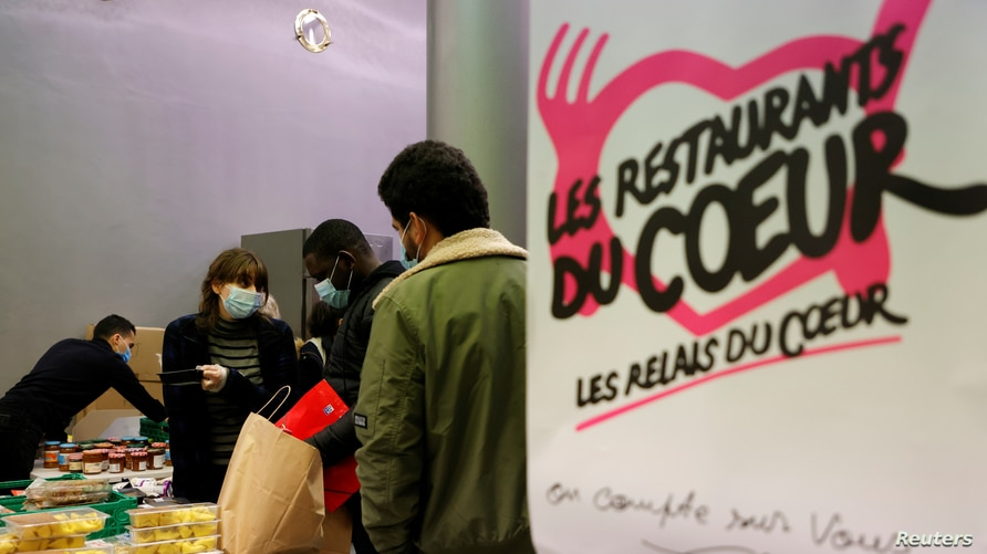 """Students get food during a distribution organized by the French charity """"Les Restos du Coeur"""" (Restaurants of the Heart) at a student residence in Paris, France, Feb. 16, 2021."""