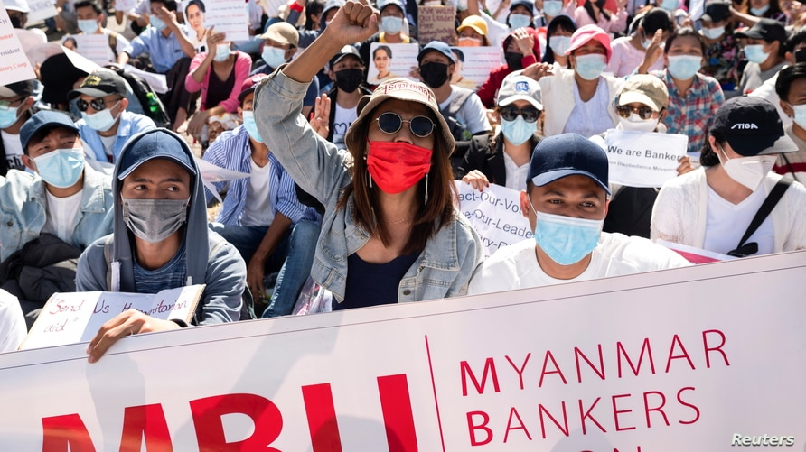 Demonstrators rally outside the Central Bank of Myanmar during a protest against the military coup and to demand the release of elected leader Aung San Suu Kyi, in Yangon, Myanmar, Feb. 11, 2021.