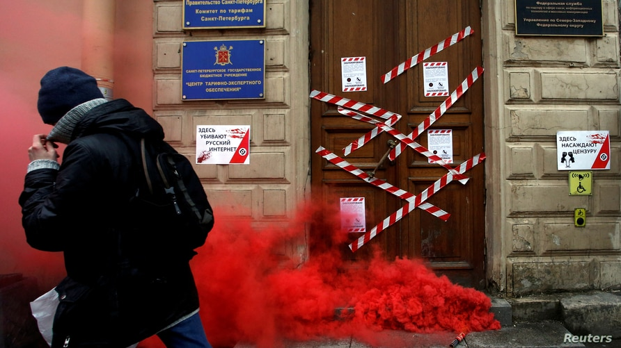 FILE - A protester walks past a defaced entrance of Russian government media watchdog Roskomnadzor's office, in central St. Petersburg, March 10, 2019.