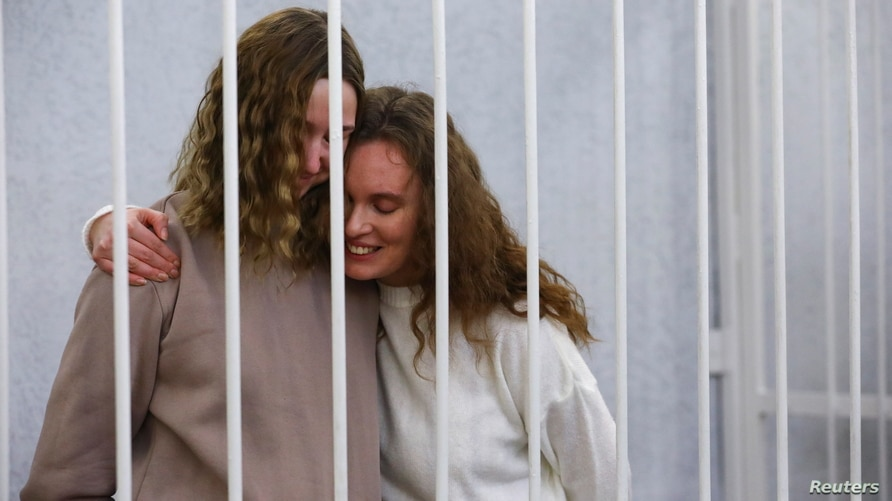 Yekaterina Andreeva and Darya Chultsova, journalists working for the Polish television channel Belsat accused of coordinating mass protests in 2020 by broadcasting live reports, embrace inside a defendants' cage during a court hearing in Minsk, Belarus.
