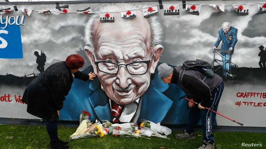 People view a mural of late record-breaking centenarian Captain Tom Moore, who died on Tuesday, in Two Gates, Tamworth, Britain, Feb. 3, 2021.