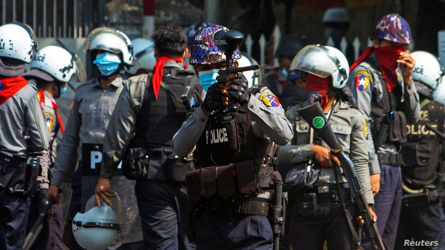 A riot police officer opens fire on protesters during a protest against the military coup in Yangon, Myanmar, Feb. 28, 2021.