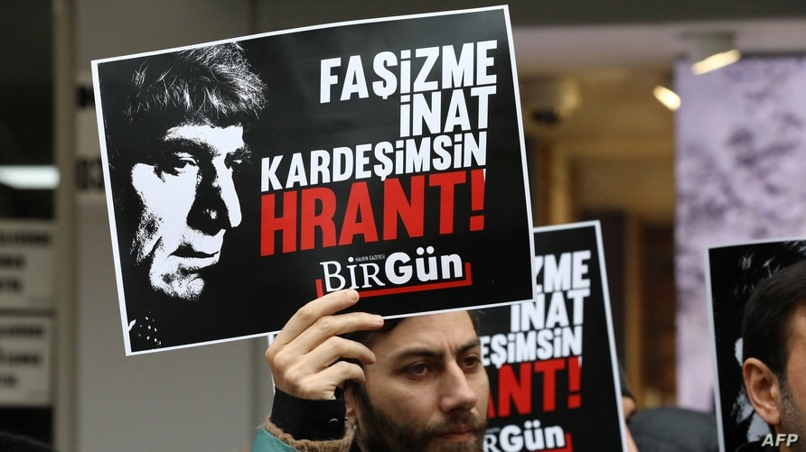 People hold placards picturing photographs of Turkish-Armenian journalist Hrant Dink during a gathering to commemorate the 13th…
