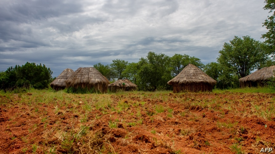 A field is seen next to houses in a village near Lubango in Angola on February 16, 2020. - The Huila province in Angola was…