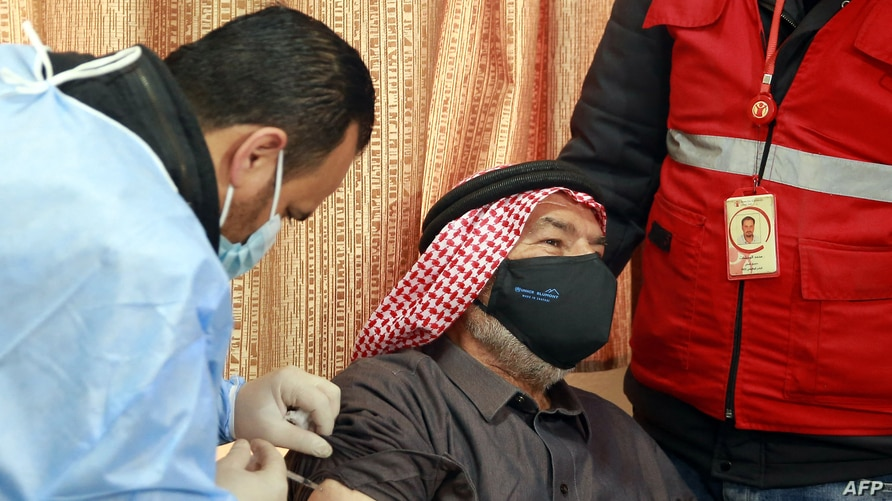 A mask-clad Jordan-based Syrian refugee receives a vaccination dose against COVID-19 coronavirus disease at a governmental…