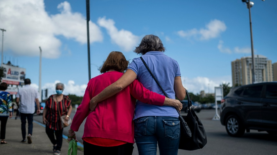 A woman and a senior citizen embrace as they walk out of a priority Covid-19 vaccination program for the elderly at a Puerto…