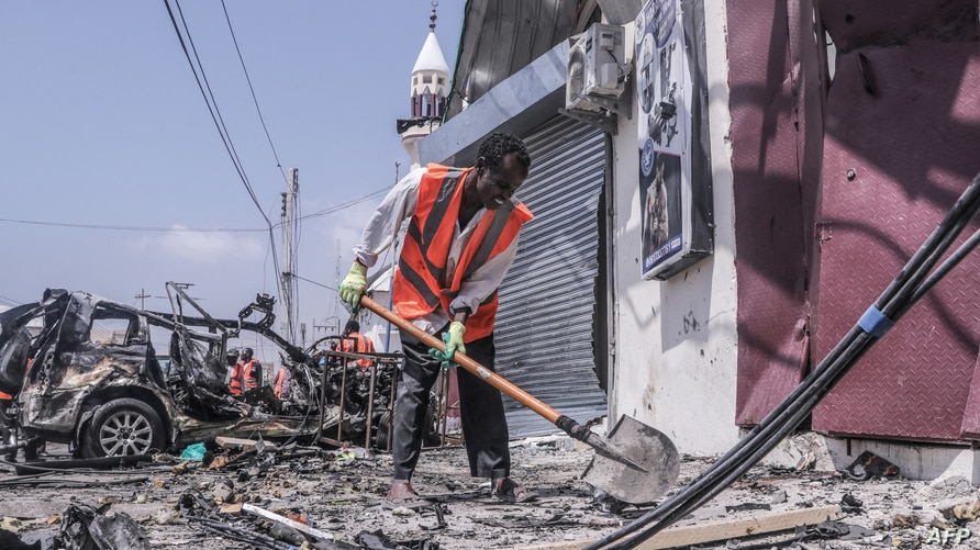 A rescue worker clears debris with a shovel at the site of a suicide car bombing attack near a security checkpoint in Mogadishu…