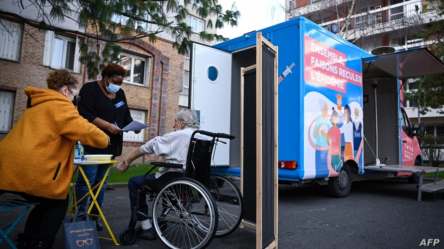 A man receives a dose of Covid-19 vaccine outside a vaccination truck parked near his residential building in the Parisian…