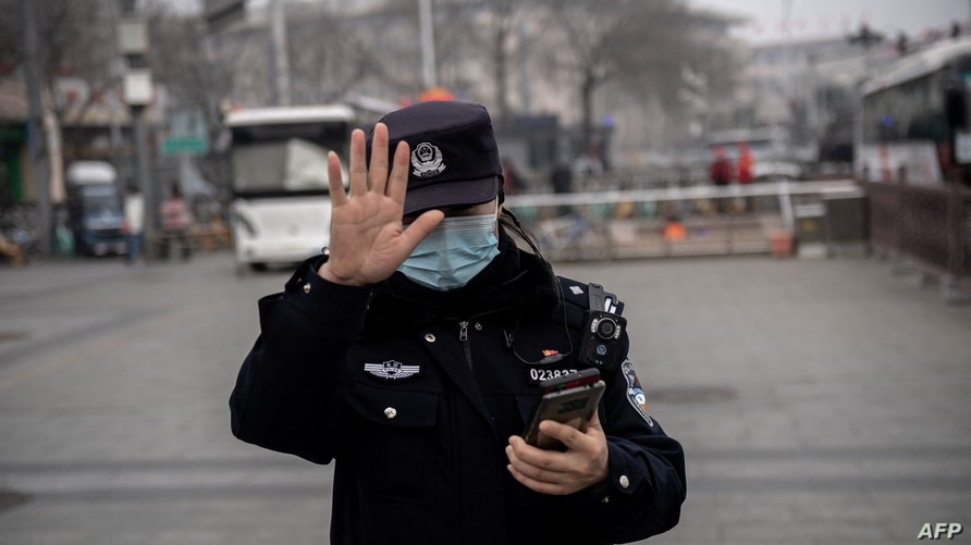 A police officer gestures to a photojournalist not to photograph near the Great Hall of the People (not pictured) during the…