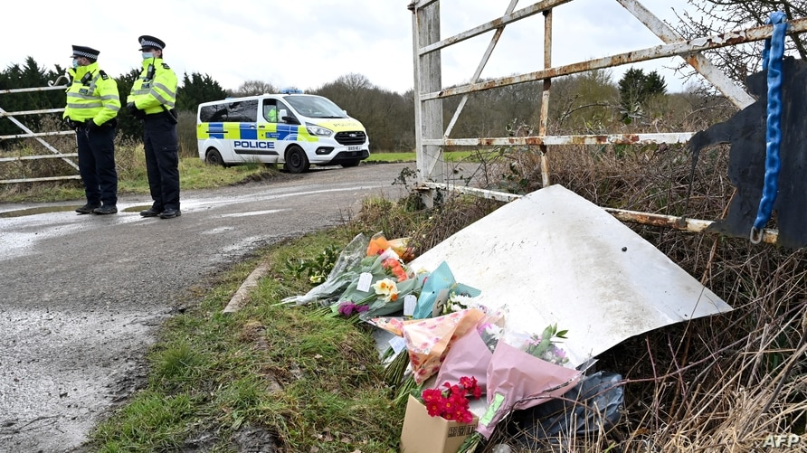 Flowers and messages of condolence for Sarah Everard are seen as police officers patrol near the woodland where police officers…
