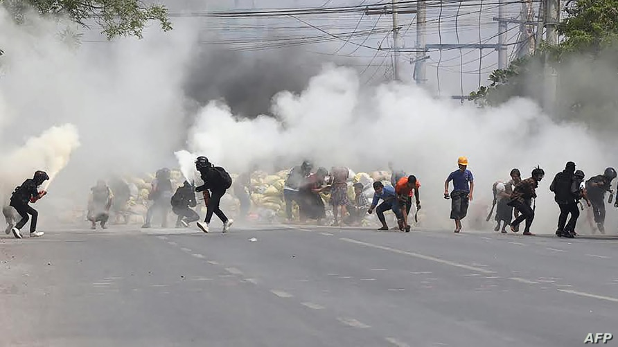Protesters run from tear gas fired by security forces, as some demonstrators also let off fire extinguishers, next to a…