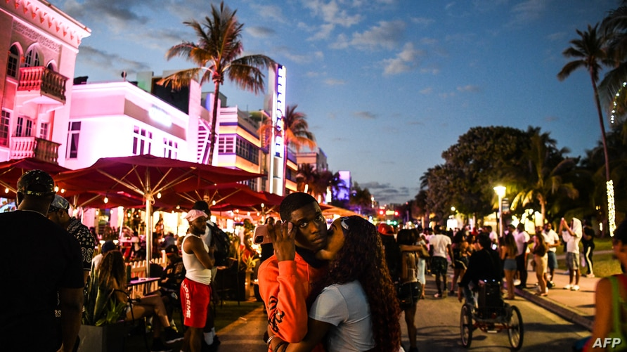 People gather on Ocean Drive in Miami Beach, on March 22, 2021. - The US city of Miami Beach, overrun by crowds of spring break…