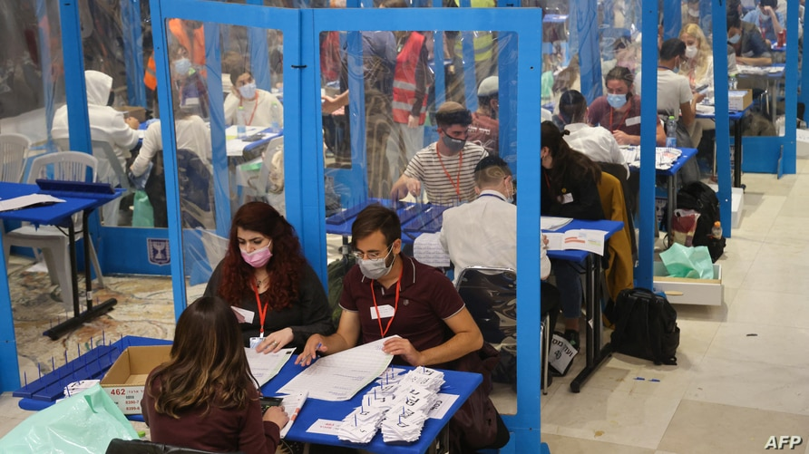 Electoral workers count ballots in Israel's general elections in Jerusalem on March 25, 2021. - As the count continues in…