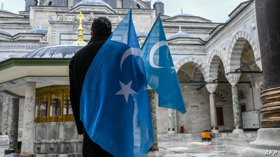 A protester from the Uyghur community living in Turkey stands with flags in the Beyazit mosque during a protest against the…