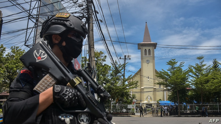 An Indonesian policeman stands guard outside a church after an explosion in Makassar on March 28, 2021. (Photo by INDRA…
