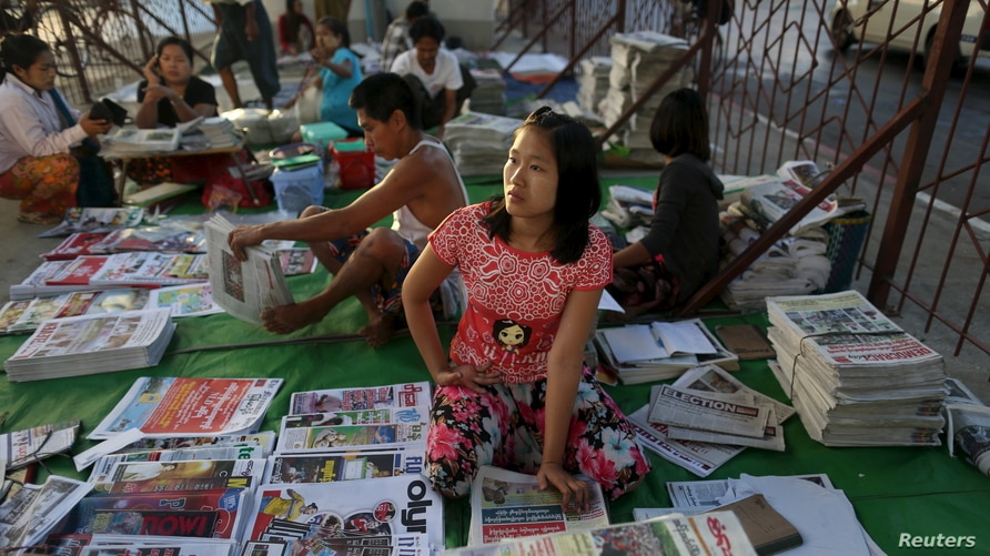 A woman sells newspapers in Yangon November 9, 2015. Voting unfolded smoothly in Myanmar on Sunday with no reports of violence…