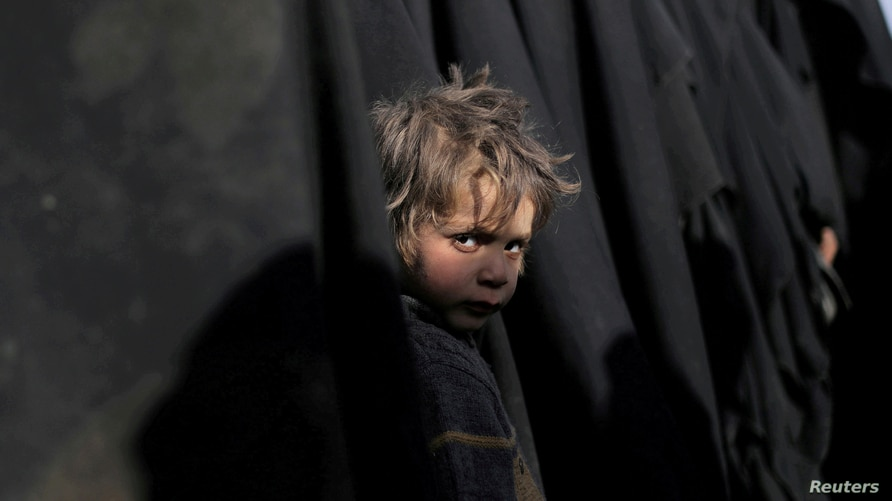 A boy waits with his mother as they queue with others for humanitarian and medical help in Deir Al Zor, Syria, March 5, 2019.