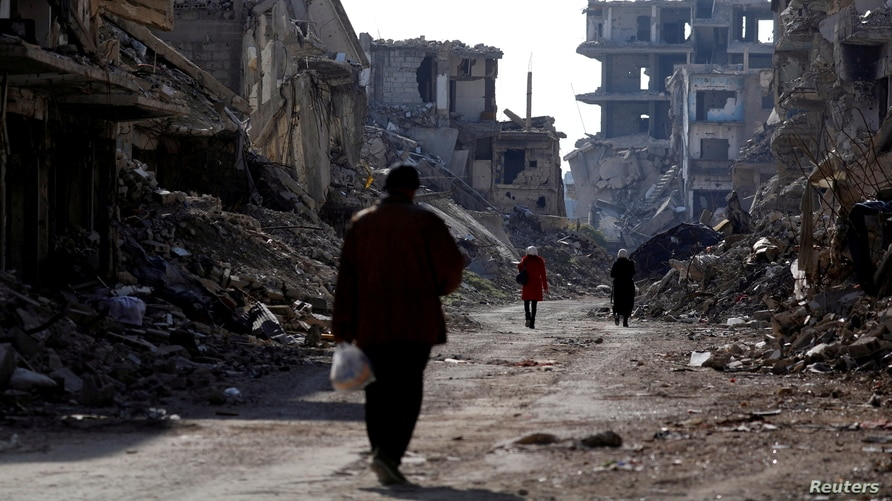 People walk past damaged buildings at the Yarmouk Palestinian refugee camp on the southern outskirts of Damascus, Syria…