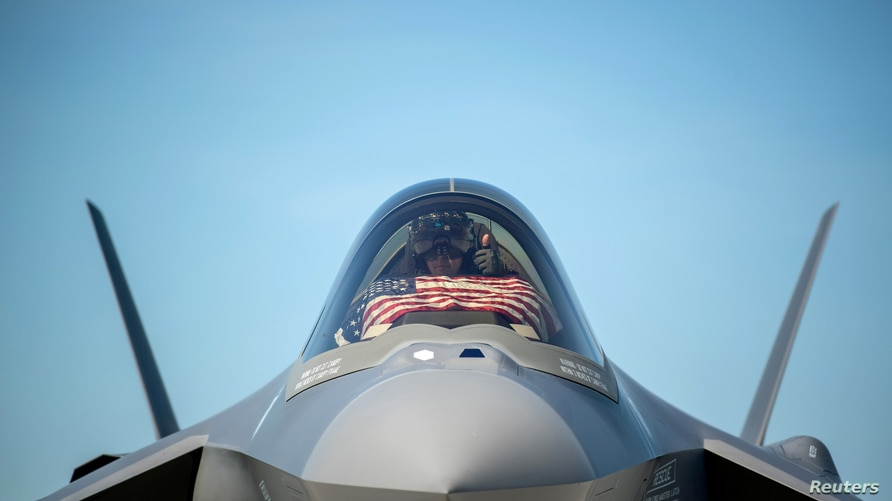 FILE - An F-35 pilot prepares for take off from the Vermont Air National Guard Base with the flag of the United States, before a flyover honoring Vermont's front line coronavirus disease (COVID-19) responders and essential workers in Vermont, May 22, 2021