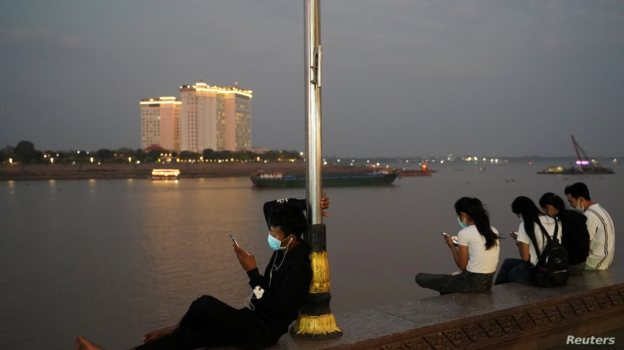 People uses their mobile phones on the Tonle Sap riverside in Phnom Penh, Cambodia, February 18, 2021. REUTERS/Cindy Liu