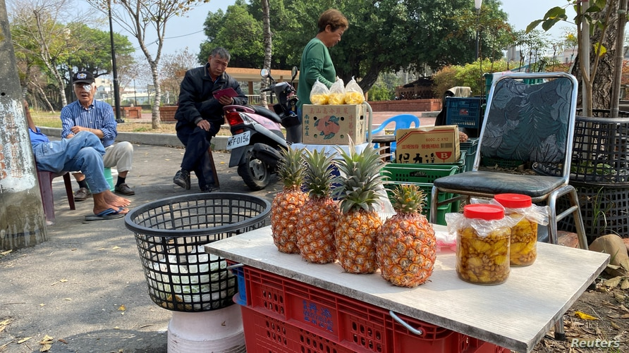 FILE PHOTO: Farmers sell pineapples at a stall by the road in Kaohsiung, Taiwan  February 27, 2021. REUTERS/Ben Blanchard/File…