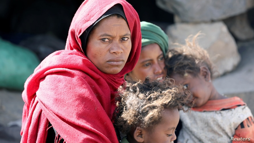 A woman looks as she sits with her children at a camp for internally displaced people on the outskirts of Sanaa, Yemen, March 1, 2021.