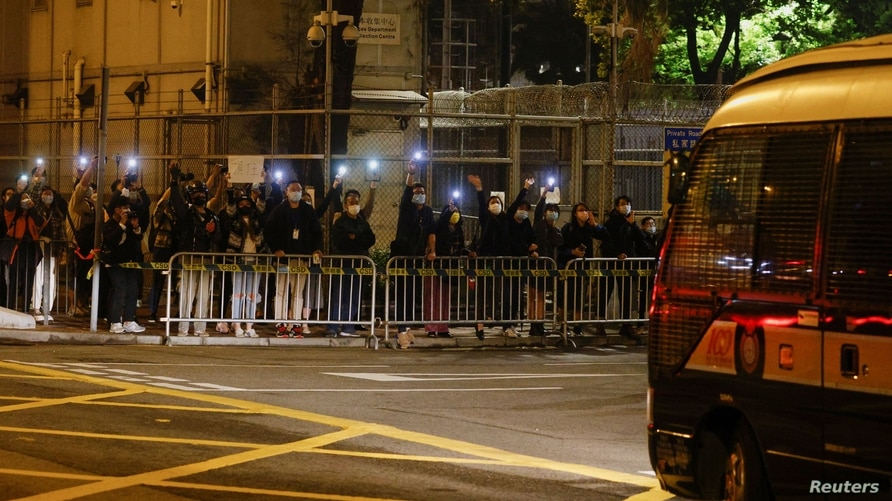 Supporters of pro-democracy activists hold their flashlights as a prison van carrying some of the 47 pro-democracy activists…
