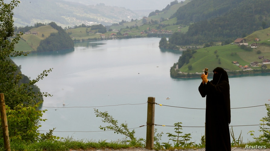 FILE - A woman wearing a niqab takes a picture from a lookout above lake Lungenersee at the Bruenigpass mountain pass road, Switzerland August 3, 2017.