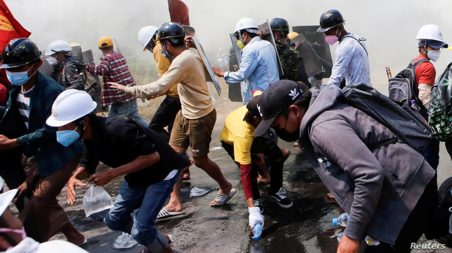 FILE - Tear gas and fire extinguisher gas surround demonstrators as they run away from police during a protest against the military coup in Naypyitaw, Myanmar, March 8, 2021.