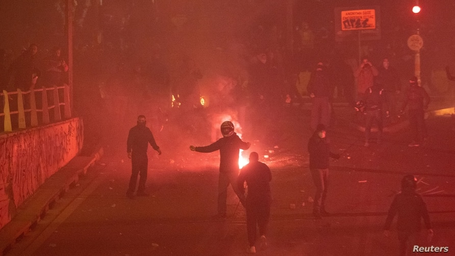 Flares burn near protesters, as they clash with police officers during a demonstration against a police crackdown on gatherings…