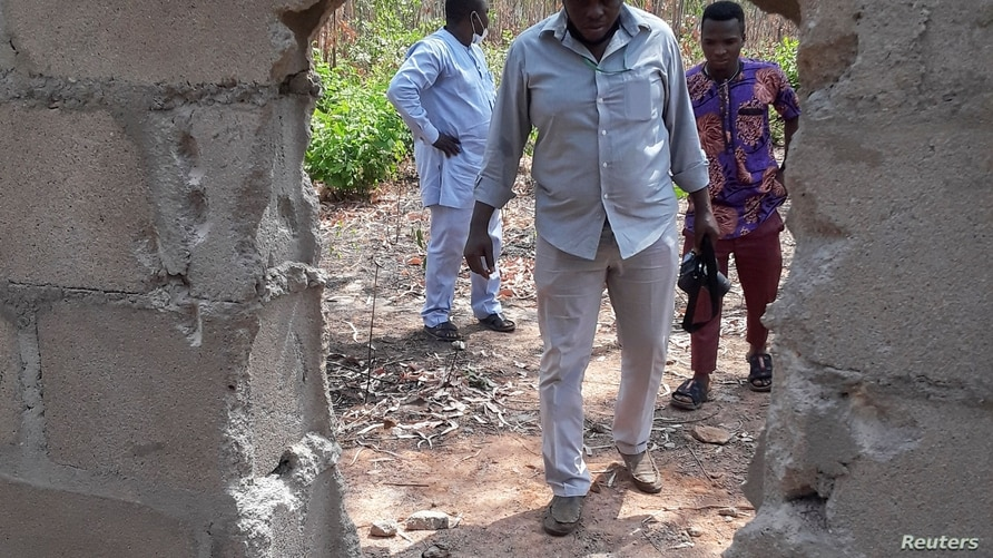 People are seen at the broken perimeter fence through which gunmen gained access the male and female hostels at the Federal…