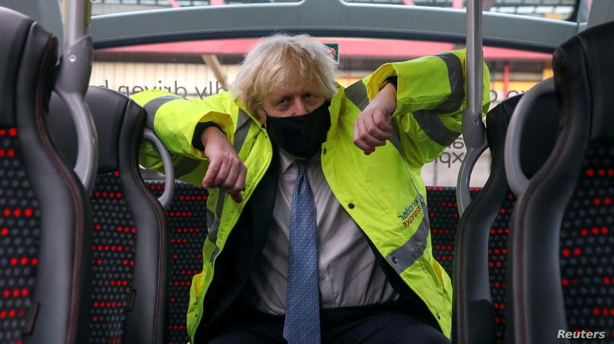 Britain's Prime Minister Boris Johnson sits on a bus during a visit to the National Express depot in Coventry, Britain, March 15, 2021.
