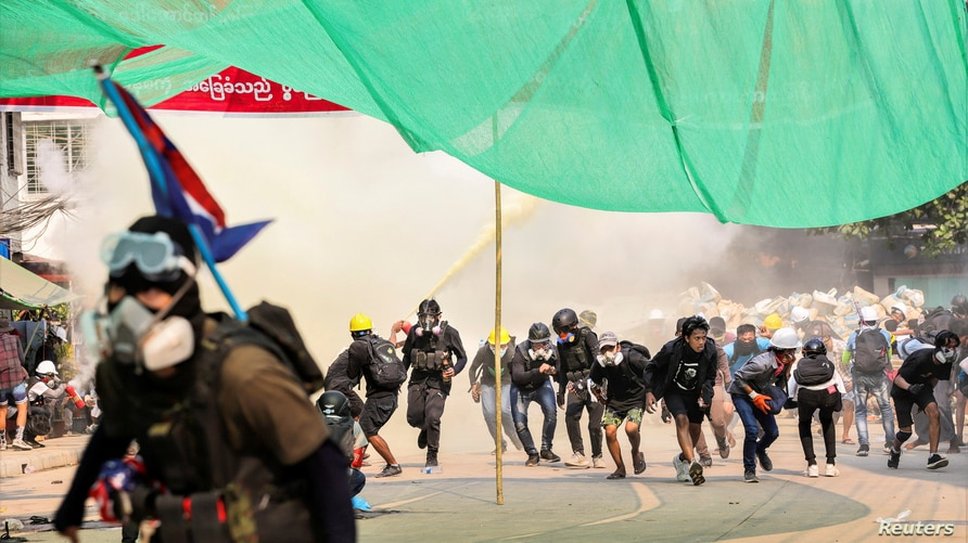 FILE PHOTO: Protesters run during a crackdown on anti-coup protests at Hlaing Township in Yangon, Myanmar March 17, 2021…