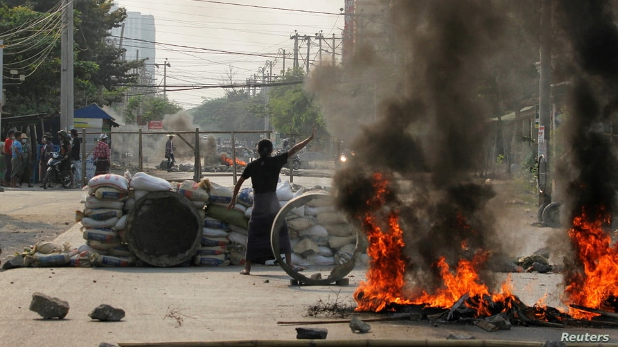 A demonstrator gestures near a barricade during a protest against the military coup in Mandalay, Myanmar March 22, 2021…
