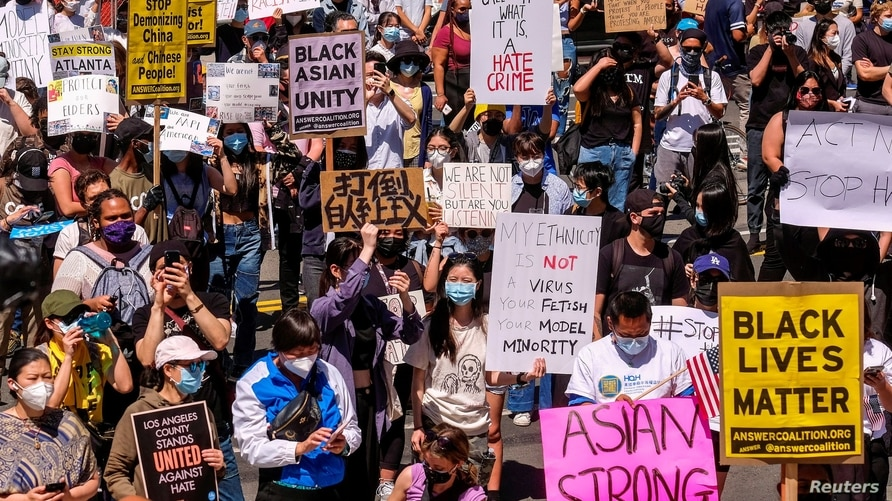 Demonstrators hold signs during a rally against anti-Asian hate crimes outside City Hall in Los Angeles, California, U.S. March…