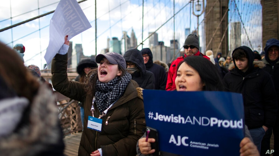 People shout slogans as they march across the Brooklyn Bridge in solidarity with the Jewish community after recent string of…