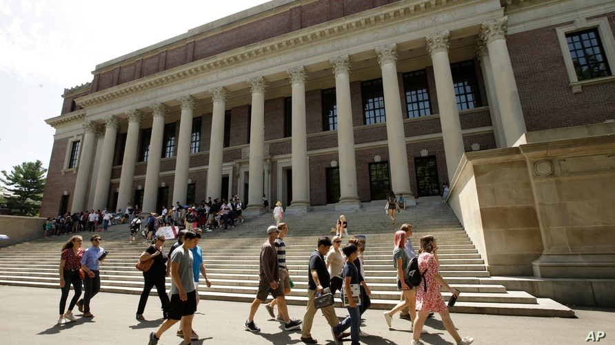 FILE - In this July 16, 2019, file photo people walk past an entrance to Widener Library, behind, on the campus of Harvard…